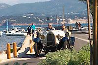View from Sanary over the sea towards the mainland mountains, Provencal boats moored at buoys in the water, an old antique collectors Talbot car with a man and a woman inside Le Brusc Six Fours Var Cote d'Azur France