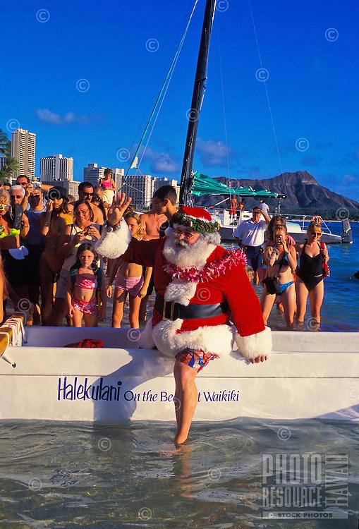 Crowds await Santa's arrival by outrigger canoe on Christmas Eve at Waikiki Beach behind the Halekulani hotel.