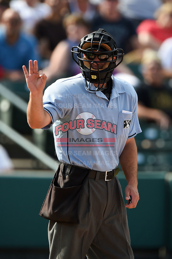 Umpire Ben May signals for three new baseballs during the first game of a doubleheader between the Buffalo Bisons Rochester Red Wings on July 6, 2014 at Frontier Field in Rochester, New  York.  Rochester defeated Buffalo 6-1.  (Mike Janes/Four Seam Images)