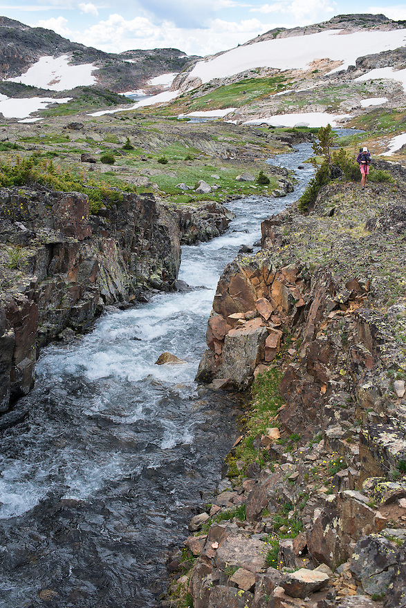 A hiker looks into a chasm below Upper Aero Lake in the Absaroka-Beartooth Wilderness.