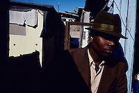 A young man stands in a suit and hat outside his home as he has recently returned from a manhood ceremony in a rural area. He lives in Khayelitsha, the largest and poorest black township outside Cape Town, South Africa. They were circumcised and taught how to prepare for manhood during a one-month stay in a hut in the bush. (Photo by: Per-Anders Pettersson)