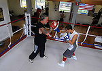 Mykquan Williams, 13, of East Hartford, works with Paul Cichon, Director of Boxing at Ring of Champions Society, Wednesday, July 20, 2011, on Main Street in Manchester. (Jim Michaud/Journal Inquirer)