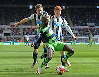 Modou Barrow of Swansea City (centre) goes down after being challenged by Jack Colback of Newcastle United (right) during the Barclays Premier League match between Newcastle United and Swansea City played at St. James' Park, Newcastle upon Tyne, on the 16th April 2016