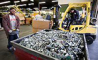 12/4/2008 4:03:10 PM -- Seattle, WA.Employee Tyrone Wiggins 22, left, of Kent, Wash., takes a bin of scrap metal while Brian Morones, 18, of Seattle brings in a box of electronics to be recycled at Total Reclaim Inc., Environmental Services in Seattle Thursday Dec. 4, 2008.