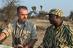 African Lion (Panthera leo) biologist, Luke Hunter, discussing poaching activities with park scout, Timbo Frackson, Kafue National Park, Zambia