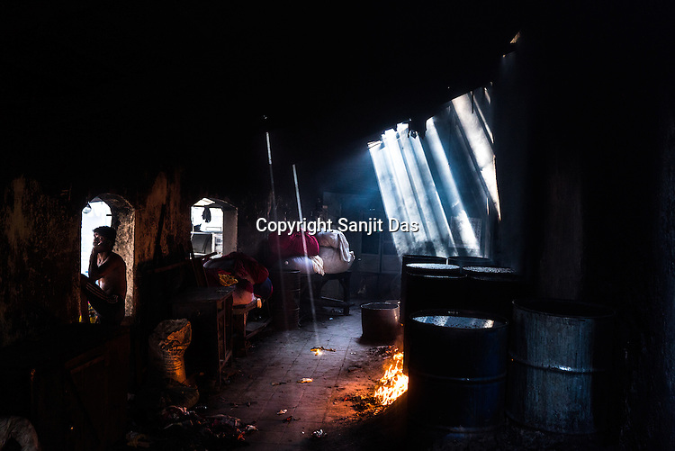 Sanjay, a dhobi (washerman) speaks on the phone next to the cauldrons of boiling water and chemical in Dhobighat in India's financial capital, Mumbai, India.