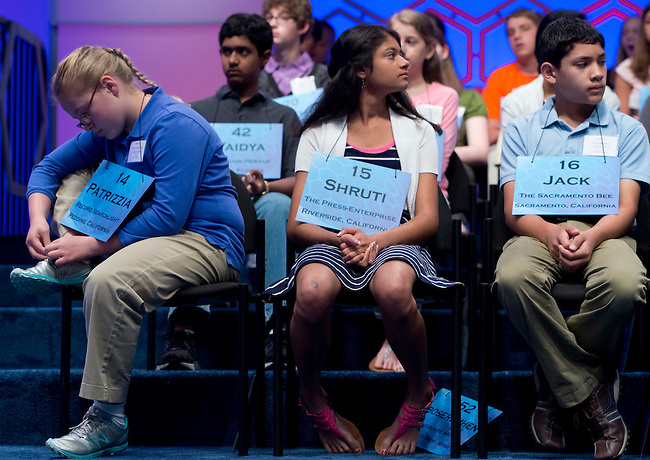 Speller 14 Patrizzia Constanza Fox-Beaudet ties her shoe on stage during the preliminary rounds of the Scripps National Spelling Bee at the Gaylord National Resort and Convention Center in National Habor, Md., on Wednesday,  May 30, 2012. Photo by Bill Clark