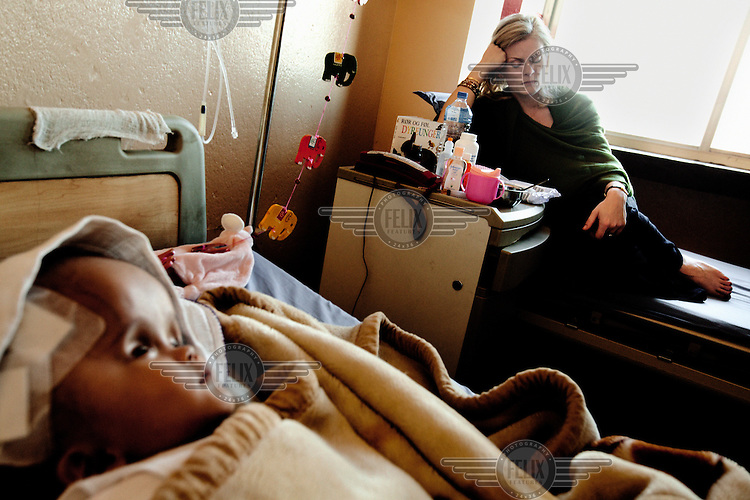 Cecilie (right) sleeps as she prepares to leave the Annapurna Neurological Institute in Kathmandu. She is exhausted and worried. Victoria (left) had surgery two days ago when 1.5 litres of fluid was drained from her brain; she is now feverish and crying a lot. 19 month old Victoria (formerly named Ghane) was born with hydrocephalus and was left abandoned. Cecilie Hansen was so moved by the story of Ghane she read in a Danish newspaper that she decided to fly to Kathmandu to try to assist her and show her the love of another human being; Cecilie eventually became her legal guardian. Victoria died on November 19 2010 from heart failure.