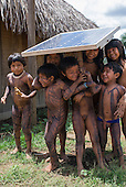 Ngoiwere Village, Mato Grosso State, Brazil. Kisedje (Suya); children with body paint playing under the shade of a solar panel, used for the village's shortwave radio (communications).