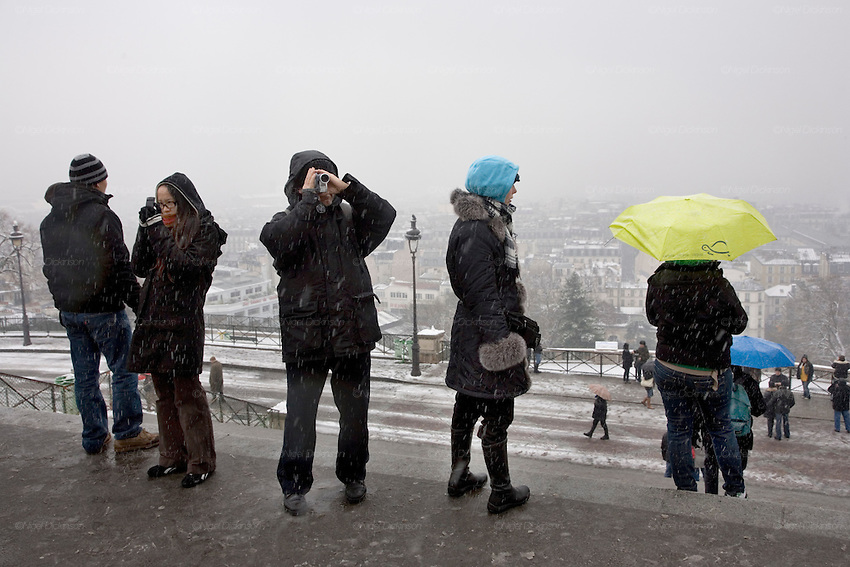 CLIMATE CHANGE. Snow, Arctic temperatures and big freeze in Paris, France. Tourists photograph the Sacre-Coeur  and views overlooking Paris, never mind the snow blizzard going on around them. Temperatures plummeted below zero, as low as -9. Very rarely, certainly not for decades, that Paris has experienced such freezing cold weather. Snow normally disappears in a couple of hours, this time it stuck around for days. Freak weather conditions and climate change can often be attributed to global warming and the ozone layer.