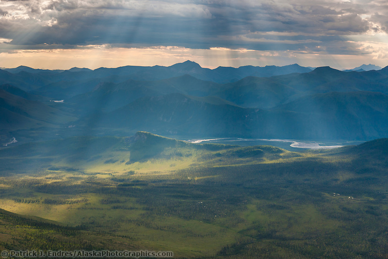 Aerial of dramatic clouds and sunlight over the bettles river, Brooks Range mountains, Alaska.