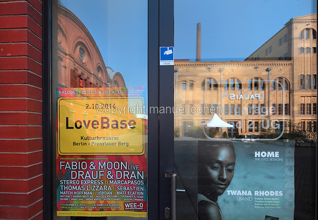 Posters stuck to the door of the Kulturbrauerei or Culture Brewery, originally a 19th century brewery building, now a cultural and entertainment centre housing cinemas, theatres, clubs and function rooms, with reflections of the buildings opposite, Prenzlauer Berg, Berlin, Germany. Picture by Manuel Cohen