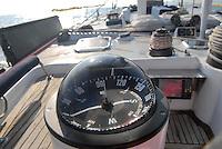 - leisure sailing boat in navigation on the Southern Mediterranean sea, detail of the compass....- barca a vela da diporto in navigazione nel mare Mediterraneo Meridionale, particolare della bussola