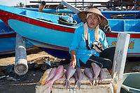 Jimbarab Beach, Bali, Indonesia.  Woman Selling Fish on the Beach, early Morning.