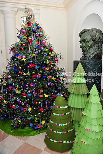 "Paper and natural Christmas tree in front of the Abraham Lincoln bust in the ""Booksellers"" area of the White House.  The theme for the White House Christmas 2011 is Shine, Give, Share - celebrating the countless ways we can lift up those around us, put our best self forward in the spirit of the season, spend time with friends and family, celebrate the joy of giving to others, and share our blessings with all.  The theme translates to the holiday décor on several levels. There is the literal translation through the use of shiny elements – star motifs, quartz and metallics like copper, aluminum and mirrored paper. There is also a conceptual connection – we're inviting visitors to give their thanks to members of our military, and have once again invited guest artists to share their talents working with the White House. This year's décor also includes handmade decorations crafted from simple materials – paper, felt, and even recycled cans. These are projects that anyone can do at home using readily available materials that are inexpensive or free..Credit: Ron Sachs / CNP"
