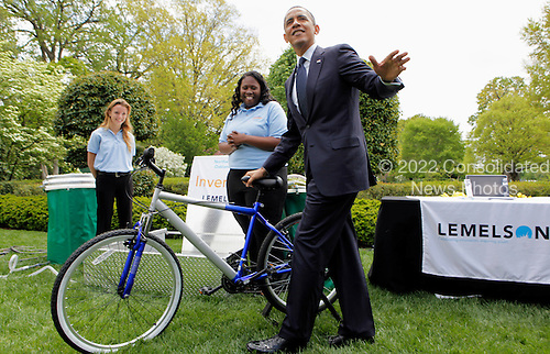 United States President Barack Obama tries the bicycle-powered emergency water-sanitation station, created and presented by high schoolers Payton Karr (L) and Kiona Elliot (R) from Oakland Park, Florida, in the East Garden of the White House in Washington, D.C., during the White House Science Fair on April 22, 2013. The White House Science Fair celebrates the student winners of a broad range of science, technology, engineering and math (STEM) competitions from across the country. The first White House Science Fair was held in late 2010. <br /> Credit: Aude Guerrucci / Pool via CNP