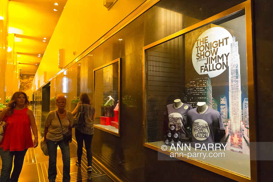 Manhattan, New York, U.S. - May 21, 2014 - At 30 Rockefeller Center in Rockefeller Plaza, visitors walk by NBC studios display case showing souvenir T-shirts and mugs for The Tonight Show starring Jimmy Fallon, during a pleasant Spring day in midtwon Manhattan.