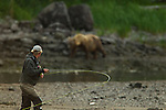 A man is seen here fishing, with a fish on the line and a brown bear in the not-too-distant background.  Photo by Gus Curtis.