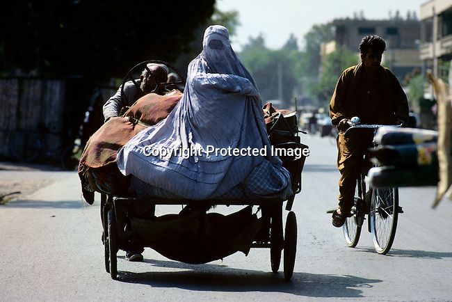 An unidentified man pushing a cart with his wife and belongings on June 22, 1996 in Kabul, Afghanistan. The Taliban took over most of Afghanistan in late 1996, and have forced people to live under strict Muslim sharia law. Girls were not allowed to attend schools and women not allowed to work. (Photo by: Per-Anders Pettersson)