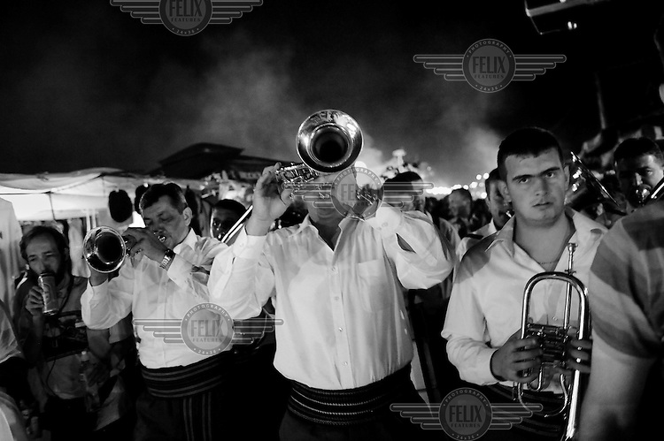 The band, winners of the trumpet festival's competition, plays its way through the streets of Guca on the last night of the trumpet festival. Hundreds of thousands of visitors gather each year in the small village of Guca for a festival of traditional brass band and folk music, the Dragocevo Trumpet Festival. Revellers party into the night on the festival's last day..