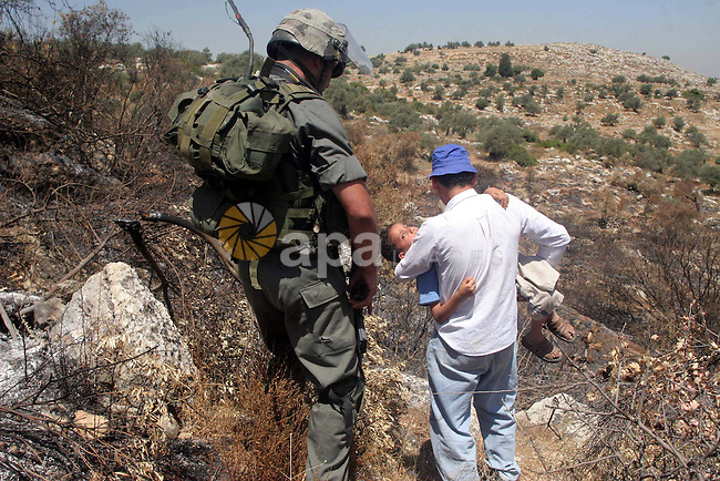 Israeli border police officers stand guard as a young Palestinian boy is evacuated down the mountainside after succumbing to tear-gas during a violent protest against the construction of Israel's controversial security fence in the West Bank village of Nilin, west of Ramallah.