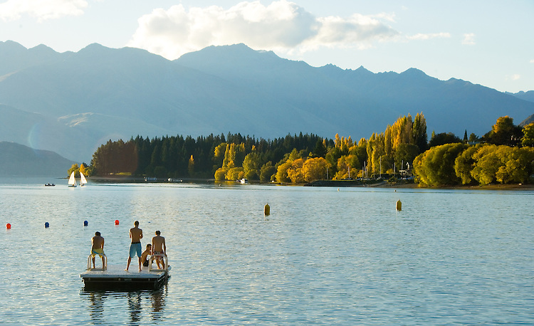 Late afternoon swimmers on pontoon at Lake Wanaka, South Island, New Zealand