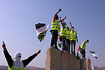"Palestinian and foreign activists flash the victory sign as they stand on top of Israel's controversial separation barrier during a protest in the Qalandia refugee camp, near the West Bank city of Ramallah, on November 9, 2009 to mark the 20th anniversary of the fall of the Berlin Wall in Germany. Palestinians are using the anniversary of the end of the Berlin wall to press their campaign against Israel's ""wall"", mostly a razor-wire fence interspersed with concrete barricades which Israel began building around the West Bank in 2002. The Jewish state has come under international censure for the barrier's de facto annexation of occupied West Bank land.. Photo by Issam Rimawi"