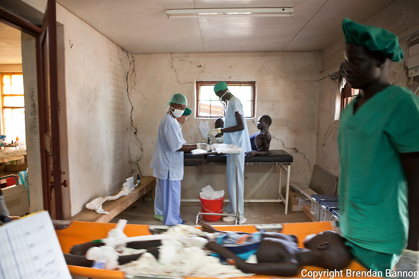 MSF  surgical staff prepare Nyadieng, 9 years old, girl accidentally shot through the hips by her 5 year old brother, for routine wound cleaning. She has her wound cleaned every other day. Her father, Yien, is caring for her while she  recovers. The accident happened on 5 March in Ayod, South Sudan.
