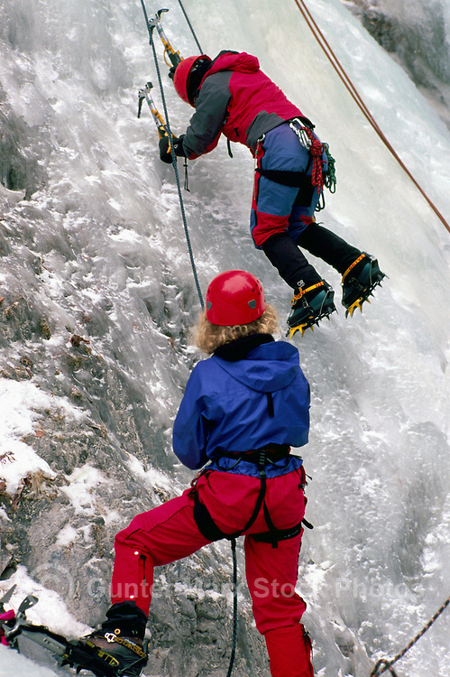 Female Ice Climber learning to climb on Frozen Waterfall at Ice Climbing Clinic, Marble Canyon Provincial Park, Southwestern British Columbia, Canada