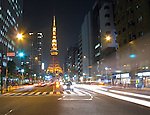 View of busy street at night with Tokyo Tower in the distance in Tokyo, Japan.