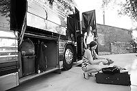 Zia McCabe of The Dandy Warhols grabs clothes out of her suitcase on the tour bus before playing a show at Mercy Lounge in Nashville, Tennessee on May 5th, 2014.