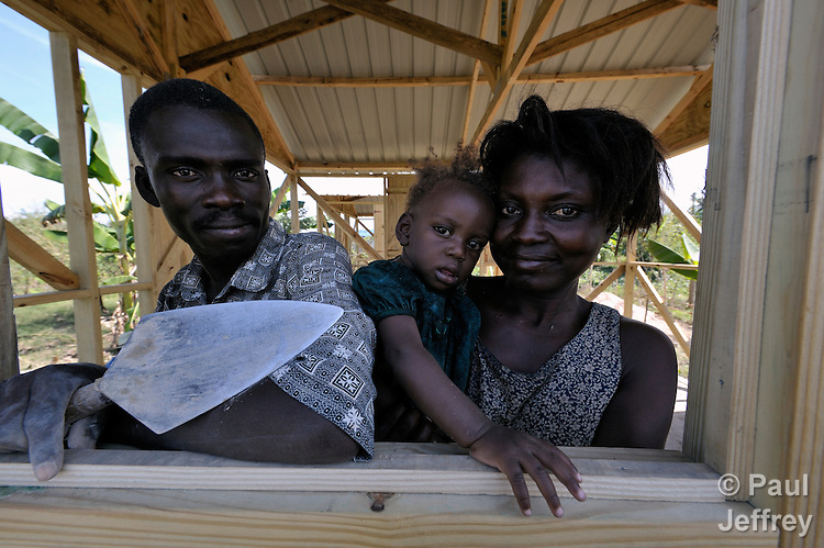 A survivor of Haiti's devastating earthquake, Kesnel Resilia (left) takes a break from working on a new house in Leogane, south of the Haitian capital of Port-au-Prince, to pose with his wife Olginne Pierre and their daughter Olginnes. The houses here are being built with with assistance from the Christian Reformed World Relief Committee, a member of the ACT Alliance. CRWRC is planning more than 1700 houses in the community, and had about half that number completed by the first anniversary of the January 21, 2010 quake. The houses are built on the foundations of the residents' former homes, and are transitional--designed to be improved by residents as they are able. CRWRC has also worked with community members on water and sanitation issues in response to the cholera outbreak, and is providing psycho-social support for residents as they rebuild their lives.