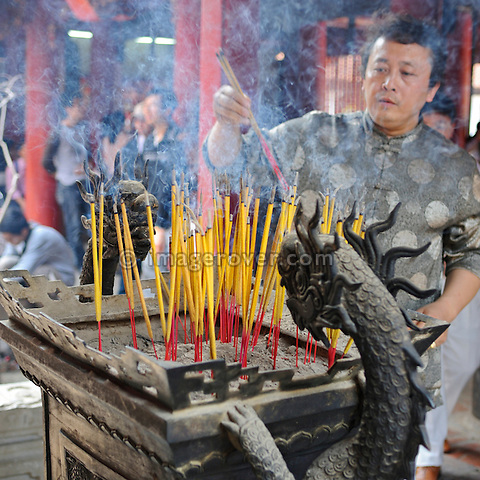 Asia, Vietnam, Hanoi. Temple of Literature (Van Mieu). House of Ceremonies (Bai Duong). Worshipping by burning incense sticks.