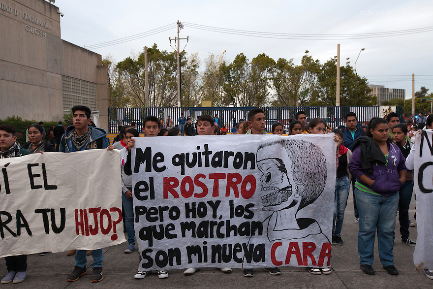 """NormalSchoolstudents from the Atequiza's teacher-trainingcollege """"Miguel Hidalgo"""" hold placards during a performance in protest for the disappearance of 43 students from Ayotzinapa's teacher training college, at the University Center for Social Sciences and Humanities in Guadalajara, Jalisco, Mexico on November 18, 2014. Parents and relatives of the 43 missing students, still do not believe the official line that the young men are all dead, and with classmates, social organizations and human rights defenders, they started on Thursday a national caravan. They split up into three different caravans, branching out to share information face to face with supporters in other cities and rally nationwide support. The three groups will meet in Mexico City on Thursday 20 for a general strike and massive marches to demand justice and fight against corrupted government and organized crime. Criticism of the government has intensified in Mexico, and many are demanding that the search for the 43 missing students continue until there is concrete evidence to the contrary. (Photo by BénédicteDesrus)"""