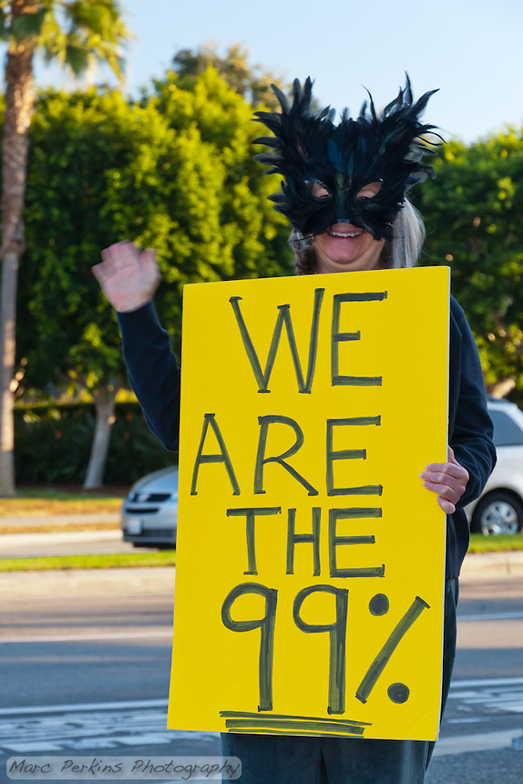"Laurel stands on a corner holding a yellow ""We are the 99%"" sign at the Occupy Orange County Irvine camp.  I took this on Halloween, hence the costume."