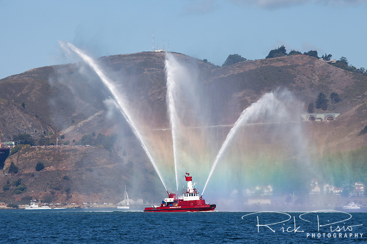San Francisco Fire Department's Guardian Fireboat No. 2 creates a rainbow as it sprays water from nozzles of its water cannons while leading the Parade of Ships during San Francisco Fleet Week.