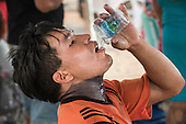 A young Kuikuro man quenches his thirst in the 44 degree heat at the first ever International Indigenous Games, in the city of Palmas, Tocantins State, Brazil. Photo © Sue Cunningham, pictures@scphotographic.com 22nd October 2015