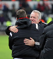 Swansea manager Alan Curtis (R) celebrates his team's win with colleagues during the Barclays Premier League match between Swansea City and Watford at the Liberty Stadium, Swansea on January 18 2016