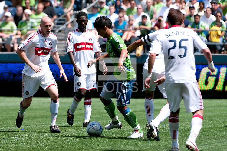 Fredy Montero (c) of the Seattle Sounders works the ball against Tim Ward (l), Patrick Nyarko (2l) and Gonzalo Segares (25) of the Chicago Fire in the match at the XBox Pitch at Quest Field on July 25, 2009. The Sounders and Fire played to a 0-0 draw.