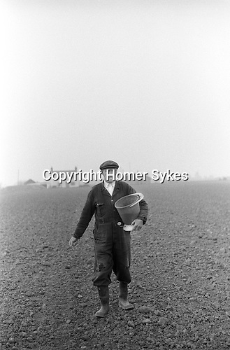 Farmer sowing seed by hand, Norfolk, England 1974