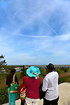South Merrick, New York, USA. 24th May 2015. At Norman J Levy Park & Preserve, family members point south to contrails in the sky over Jones Beach where planes are performing in the Bethpage New York Air Show. Many visitors watched the air show from the marshland park after area parkways to the famous Long Island beach were closed when it filled to capacity.
