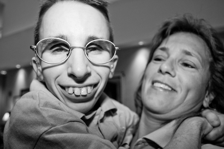 Josh Bukowski, held by Sherri Knotts, at the Share and Care Network's annual retreat held at the Doubletree Guest Suites Hotel in Boston on May 20, 2006. <br /> <br /> The Share and Care Network was created in 1981 by Pat Cahill when her son Scott was diagnosed with Cockayne Syndrome.  A rare form of dwarfism, Cockayne Syndrome is a genetically determined condition whose symptoms include microcephaly, mental retardation, progressive blindness, progressive hearing loss, premature aging, and a shortened lifespan averaging 18 years.  Those afflicted have distinctive facial features, including sunken eyes, pinched faces, and protruding jaws as well as distinctive gregarious, affectionate personalities.<br /> <br /> Because of the rarity of the condition (1/1,000 live births) and its late onset (characteristics usually begin to appear only after one year), many families and physicians are often baffled by children whose health begins to deteriorate after normal development.  It was partly with this in mind that the Share and Care Network was formed, to promote awareness of this disease as well as to provide a support network for those families affected.  In 1998 it began organizing an annual retreat, which has grown from three families in its inaugural year to more than 30 today.  Although the retreat takes place in the United States, families from as far as Japan arrive for this one weekend out of the year to share information and to support one another.