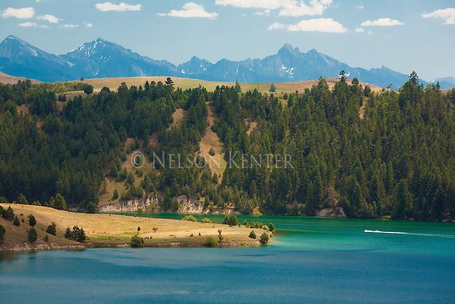 A speed boat heads back down the Flathead river towards Flathead Lake near Polson, Montana