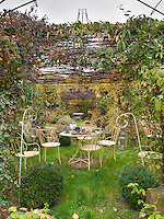 A metal table and four chairs are set out on the lawn of a secluded garden.
