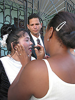 Feb 12 2003, Holguin, CUBA <br /> The bride get a last minute make up, while the grom look on, on tehir way to a Cuban civil wedding in Holguin,<br /> Photo (c) 2004) P Roussel / Images Distribution