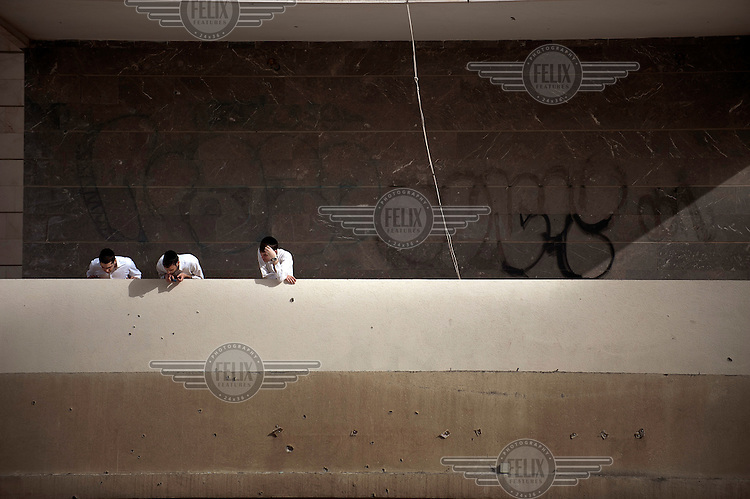 Three men look down from a balcony onto a street where a rocket fired from neighbouring Gaza has landed. The city of Ashdod, close to the border with Gaza, is often the target of rockets fired by militants from Gaza. .