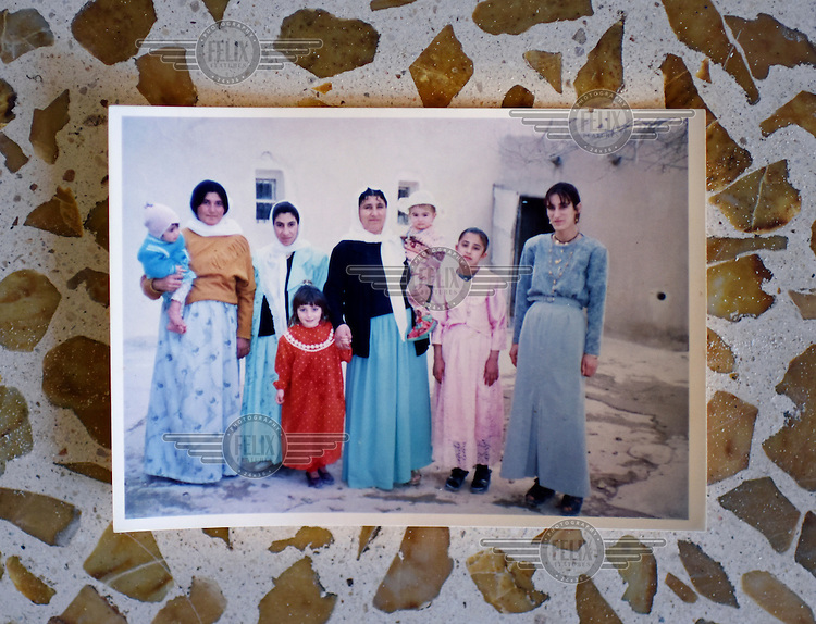 A photograph of Julia (a Yazidi girl with a red dress) and her mother's friends taken when she was younger.