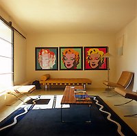 Marilyn screen prints by Andy Warhol dominate the wall of this living room which is minimally furnished with Barcelona chairs by Mies van der Rohe and a Knoll table