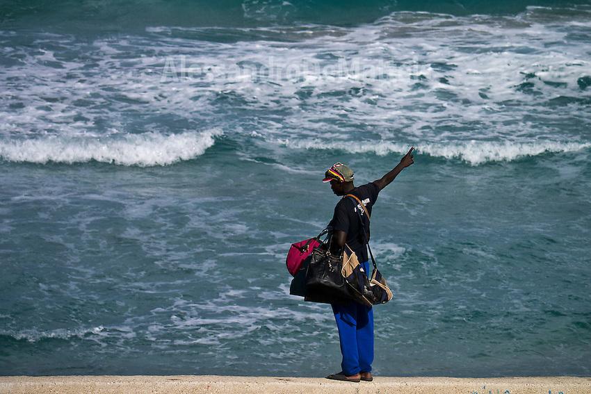 Season over - Torre dell'Orso - 2012. Un extracomunitario in spiaggia in un giorno ventoso di fine stagione quando vendere è impossibile.