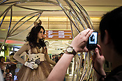 A tourist takes a picture of a woman posing as a doll inside the shopping centre of the Galaxy Resort & Hotel in Macau, China.